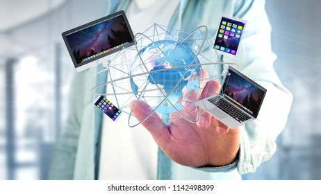 View of a Businessman holding a Computer and devices displayed on a futuristic interface with international network  - 3d render