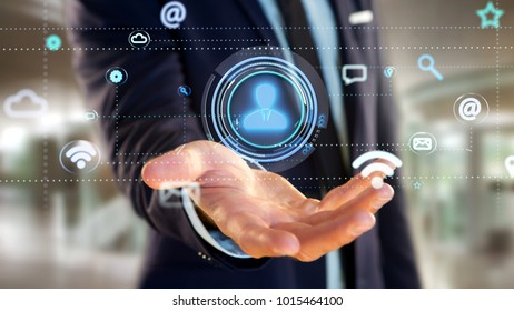 View of a Businessman holding a Contact icon surrounding by app and social icon - 3d render