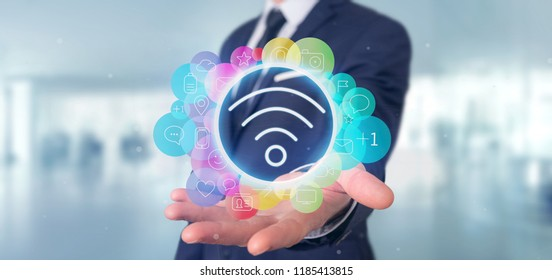 View of a Businessman holding Wifi icon surrounding by colorfull social media icon 3d rendering