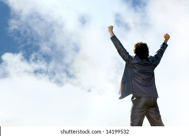 View of businessman standing a back raising his hands on the background of sky