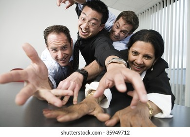 View of businesspeople reaching across a table.