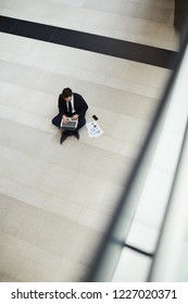 View of busy economist sitting on the floor with laptop and searching for financial data in the net