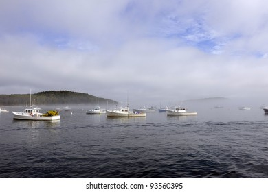 A view of a busy lobstering harbor as a morning fog is lifting.