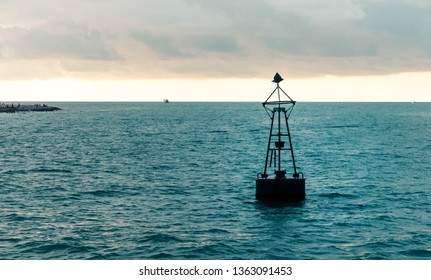 View from cabin balconies at the sea, a buoy on the water and the shore in the distance and a small ship off the side of cruise ship