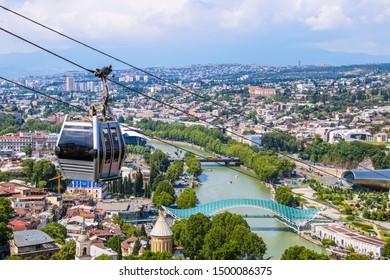 View of cable car above Tbilisi Georgia with view of Mtkvari - Kura River and Peace Bridge and city with mountains in the distance