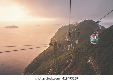 View of a cable car during beautiful sunset  in Hong Kong.  Mountain, sea or ocean landscape. Mountain covered with green forest.