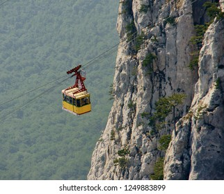 View of the cable car on the highest mountain of Crimea (Mount Ai-Petri). Cabin with passengers climbs on the rock. Evergreen pines grow on a cliff against a blurred background of trees.