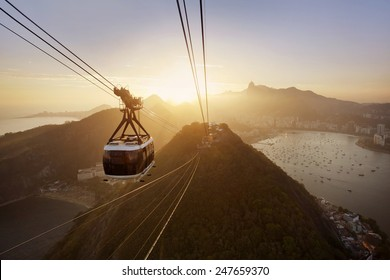 View of a cable car at sunset, showing several beaches and landmarks in Rio de Janeiro.