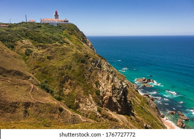 View of Cabo da Roca, Sintra, Portugal, the westernmost point of continental Europe, with its famous lighthouse, clear blue water and big green cliffs on a bright sunny day