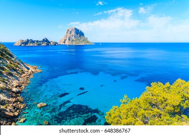 View of Cala d'Hort bay with beautiful azure blue sea water and Es Vedra island in distance, Ibiza island, Spain