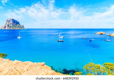 View of Cala d'Hort bay with boats on beautiful azure blue sea water and Es Vedra island in distance, Ibiza island, Spain