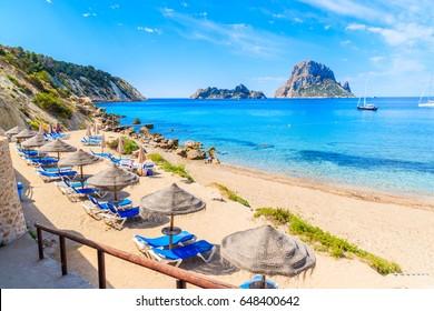 Aussicht auf den Strand von Cala d'Hort mit Liegestühlen und Sonnenschirmen und wunderschönes, blaues Meerwasser, Ibiza Insel, Spanien