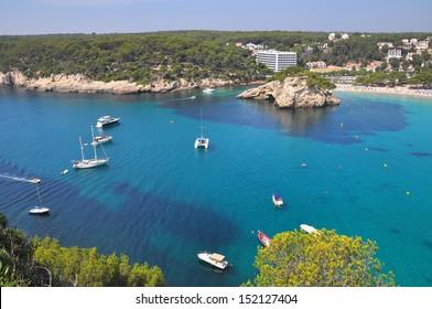 View of Cala Galdana with yachts on turquoise sea water, Menorca, Balearic Islands, Spain