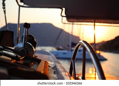 View of a calm sea-landscape from a boat at the sunset with a closeup of a Steering wheel