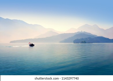 View of the calm water lake with the small boat and layers of mountains over the background in the tranquil morning, Sun Moon lake, Taiwan
