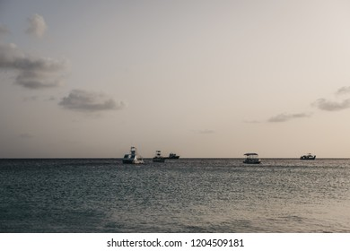 View of calm waters of Carlisle Bay in Bridgetown, Barbados, at dusk, unidentified boats on the horizon.