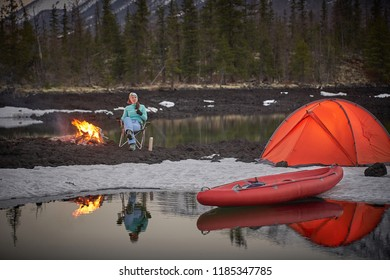 View of camp life in a mountain terrain. Lake shore with canoe