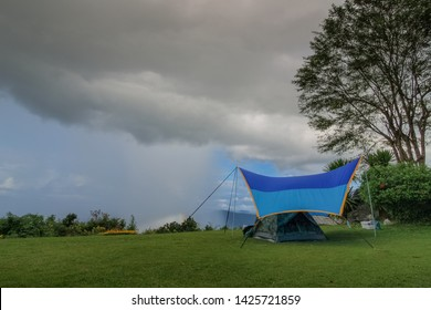 view of camping tent on green grass with rain storm and cloudy sky background, Pha Chu Camp Site, Sri Nan National Park, Nan, Thailand.