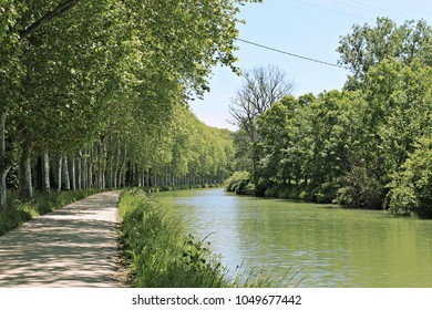 A view of Canal du Midi, France, bordered by trees.