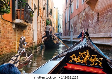 View of the Canal from a gondola in Venice, Italy. The front part of the gondola under the bridge of Venice. Gondolier pushes his foot off the house, driving the gondola