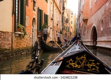 View of the Canal from a gondola in Venice, Italy. The front part of the gondola under the bridge of Venice. Gondoliers driving the gondola