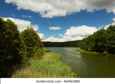 View of the canal and Karsin?skie lake in summer under blue sky and white clouds. Small village Swornegacie, Bory Tucholskie, Poland. Horizontal view.