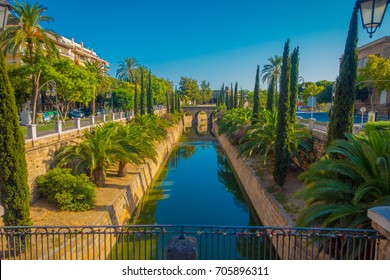 View of a canal of water crossing a park in the Historic Center of Palma de Mallorca, Spain