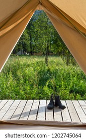 View from the canvas tent upon the woods. Pair of shoes near bell tent at forest. POV