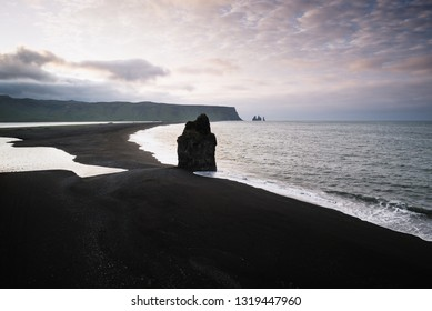 View from cape Dyrholaey on stack Arnardrangur and Reynisdrangar basalt sea stacks. Reynisfjara beach with black volcanic sand. Tourist attraction in the south of Iceland