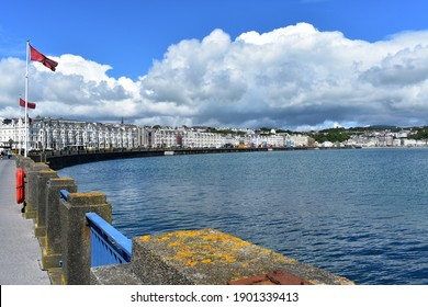 A view of the capital of Isle of Man, Douglas. Manx flags are flying and we can see a row of identical white buildings in line. There is a fairground along the promenade.