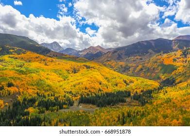 View from the Capitol Creek Trailhead in Autumn near Aspen, Colorado. Golden aspen trees blanket the mountainside.