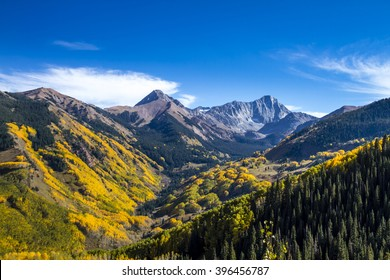 View of Capitol Peak near Aspen Colorado surrounded by valley filled with changing yellow Aspen trees on sunny autumn afternoon