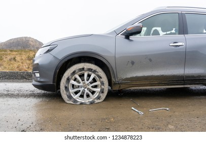 View of a car with flat tire on a gravel road and tools for repair