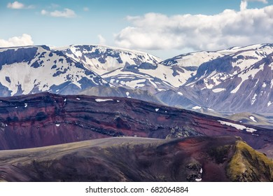 View of the car and horses on the background of mountains tops under a cloudy sky in Iceland