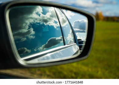 View in the car mirror.Highway, autobahn and road landscape. Automobile, cars and vehicles. Blue sky and sunny day. European autobahn. Nature and urban together.