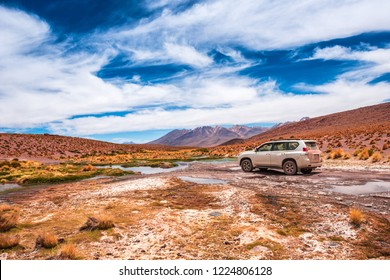 View of a car on the background of breathtaking landscape of Bolivia