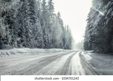 View from a car riding through snow covered winter road curve, lit by strong sun backlight and fog and haze in distance - dangerous driving conditions.