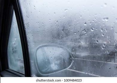 View of a car side mirror from inside the car with condensation and rain on the glass window