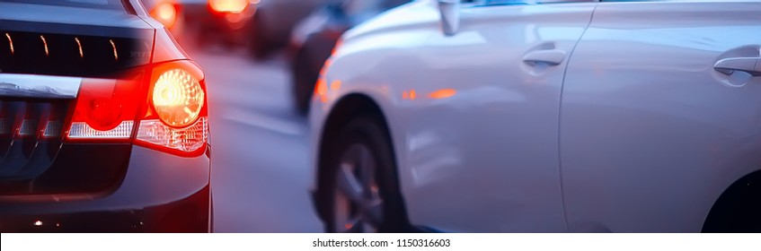 view of car in  traffic jam / rear view of the landscape from window in car, road with cars, lights and the legs of the cars  night view