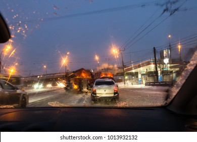 view of car traffic and street sweeping machines through wet windscreen while driving car on road in Moscow city in winter evening in snow
