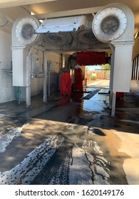 View of car wash from outside with soapy water on the pavement