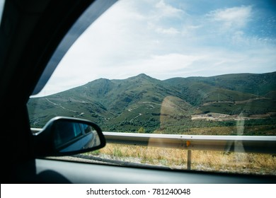 View from car window on green hills and blue sky, Spain