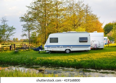 View of caravan trailers parked on a green lawn in a camping on a spring day
