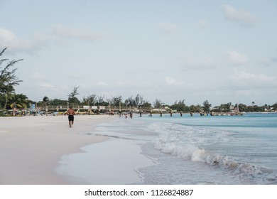 View of Carlisle Bay beach in Bridgetown, Barbados, unidentified man running along the water. It is a popular tourist destination and lies in the heart of a UNESCO World Heritage Site.