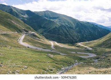 View to the carpathian mountains war road transfagarasan from the top with lonely trees and clouds above - vintage film look