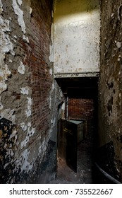 A view of a cast iron staircase with peeling and chipped paint on the plaster walls leading down to an open door at the long abandoned Hudson River State Hospital in New York.