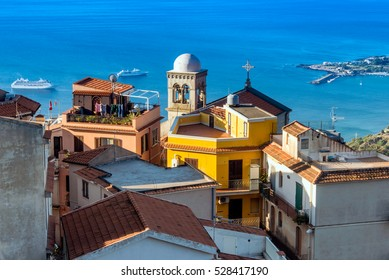 View from Castelmola, Sicily: the bell tower in the light of the morning sun and 2 cruise ships in the sea.