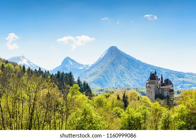 View of the Castle of Menthon-Saint-Bernard (Château de Menthon-Saint-Bernard) surrounding the forest and the Alps. Switzerland