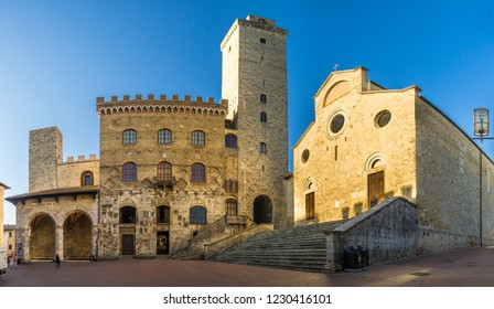 View at the Cathedral of Santa Maria Assunta with Town hall building at the Place of Duomo in San Gimignano, Italy