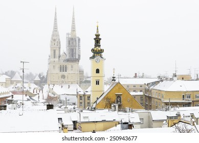 A view of the cathedral of Zagreb, Croatia, and picturesque roofs covered in snow.